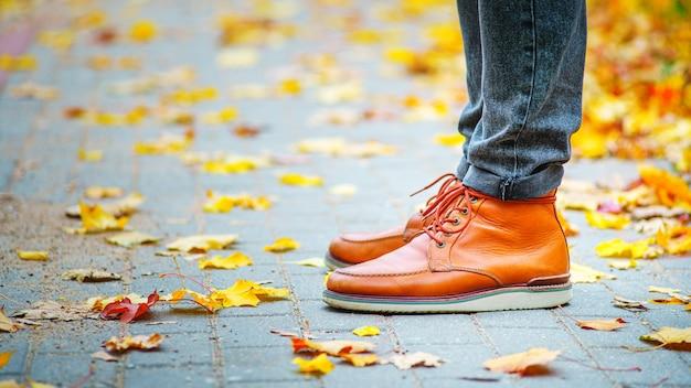 Benen van een man in bruine laarzen op de stoep bezaaid met gevallen bladeren.