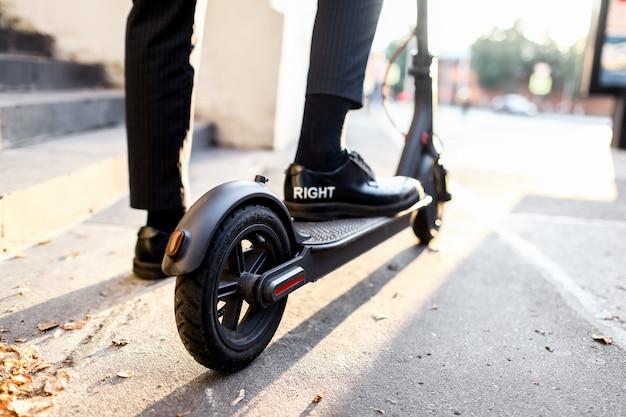 Benen van een man in stijlvolle outfit staan op elektrische scooter op straat
