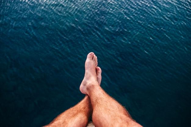 Benen van een man rustend op de zee met een dorp