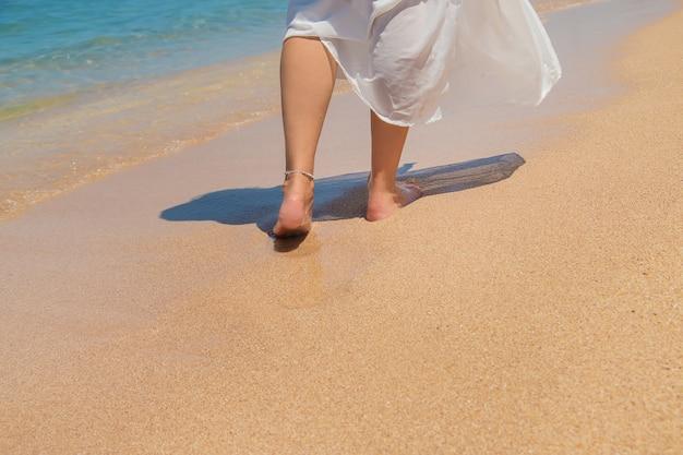Benen van een meisje aan de kust
