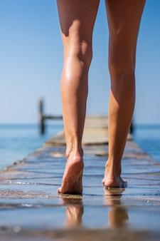 Benen van een meisje dat op een houten brug in het midden van de oceaan loopt