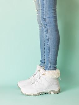 Benen van een meisje in een sportieve winterstijl op blauw. wintersportstijl.