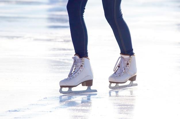 Benen van een meisje in spijkerbroek en witte schaatsen op een ijsbaan. hobby's en vrije tijd. wintersport