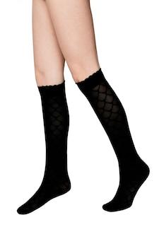 Benen van een meisje in zwarte sokken op een witte achtergrond