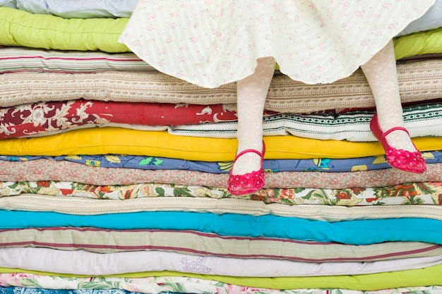Benen van een meisje zittend op een stapel matrassen decoraties voor het sprookje de prinses op een erwt