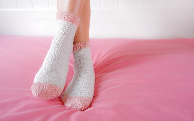 Benen van een mooie vrouw dragen warme sokken op de slaapkamer. mode roze sokken.