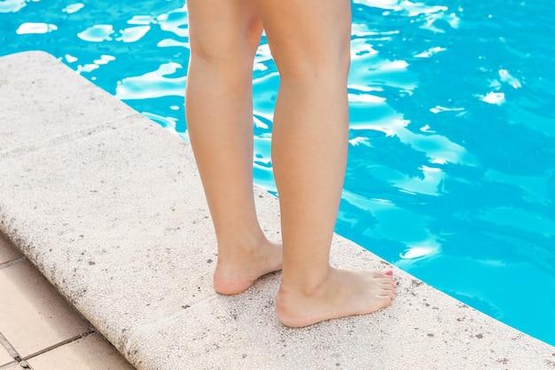 Benen van een mooie vrouw voor het blauwe water van een zwembad tijdens de zomer