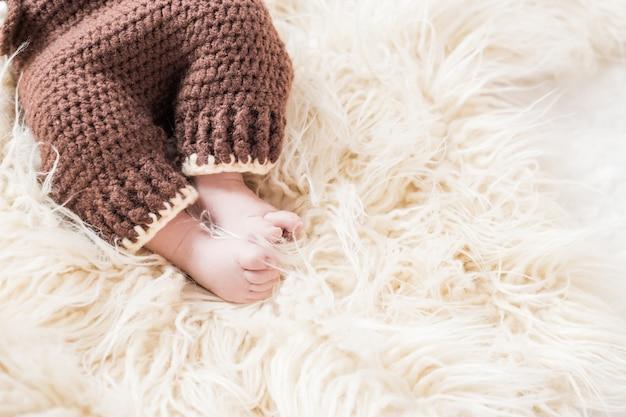 Benen van een pasgeboren baby op een witte wollige