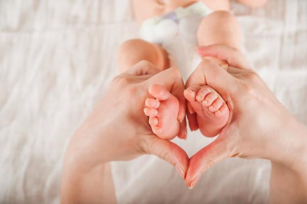 Benen van een pasgeborene in handenclose-up. baby's voeten en kopieer de ruimte. babyverzorging en koliek