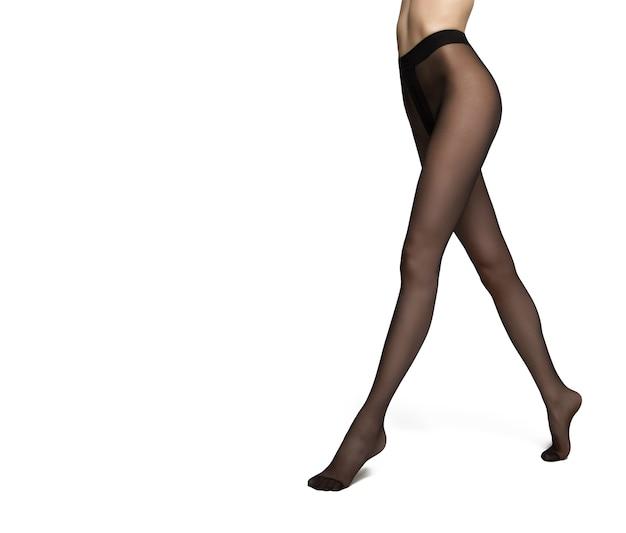 Benen van een vrouw in zwarte nylon panty's op witte achtergrond
