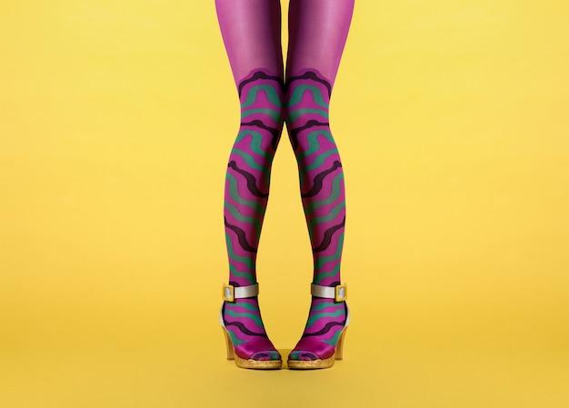 Benen van een vrouw met knikknieën en duiventenen in paarse collant