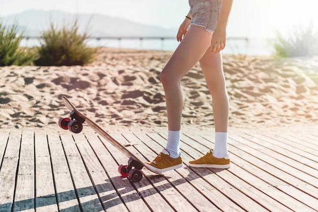 Benen van een vrouwelijke skater die de skate naar beneden duwt in korte broek