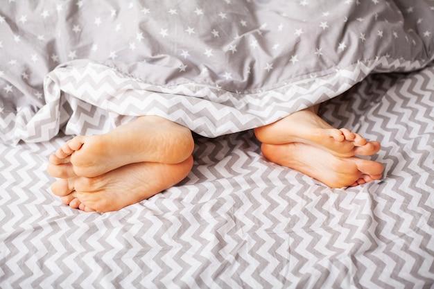 Benen van geliefden onder deken. gelukkig paar dat pret in bed heeft.