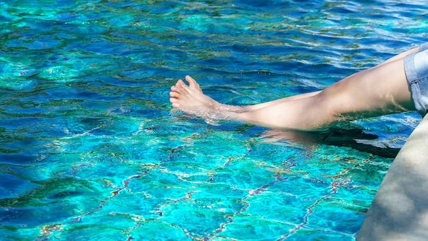 Benen van het aziatische tiener ontspannen bij zwembad