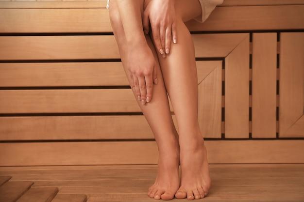 Benen van het jonge vrouw ontspannen in de sauna