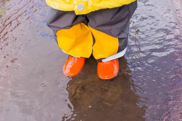 Benen van het kind in oranje rubberen laarzen springen in de herfst plassen. heldere rubberlaarzen voor kinderen