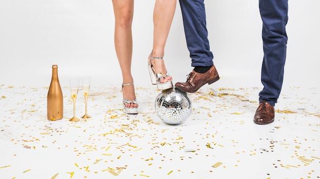 Benen van het paar op disco bal op feestje