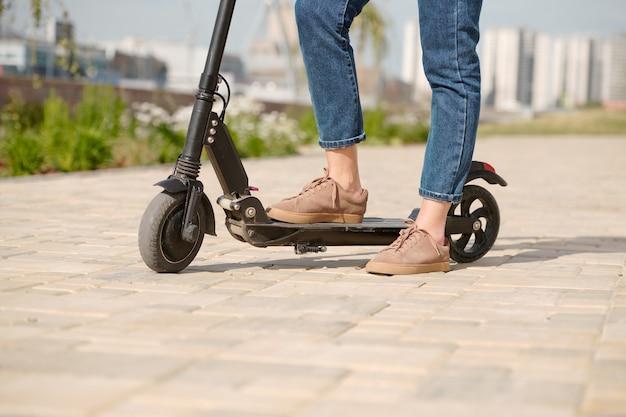 Benen van jonge moderne vrouw in spijkerbroek en laarzen staan op scooter en stedelijke weg terwijl ze een korte pauze neemt op weg naar haar werk