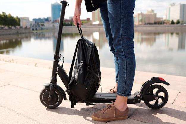 Benen van jonge vrouw in blauwe spijkerbroek met zwarte lederen rugzak over elektrische scooter terwijl ze tegen de rivier en stadsgezicht staan