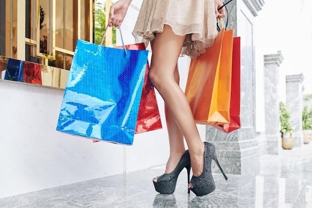 Benen van jonge vrouw in hoge heuvels met veel papieren zakken na het winkelen
