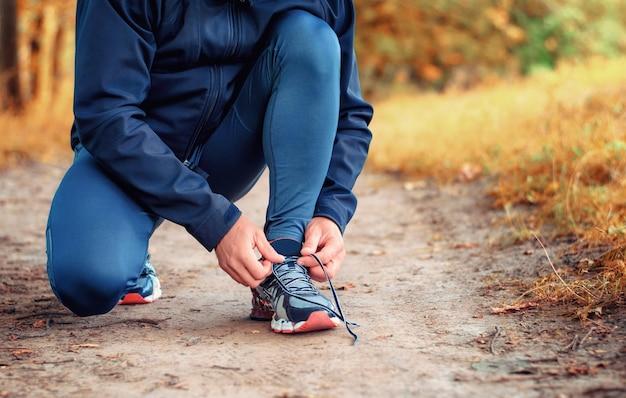 Benen van loper in een zwarte sportlegging en sneakers banden veters op een pad in geel herfstbos.
