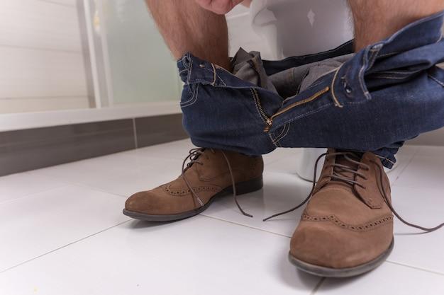 Benen van man met spijkerbroek zittend op een toiletpot in de moderne betegelde badkamer thuis