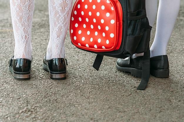 Benen van meisjes in schooluniform met een rugzak