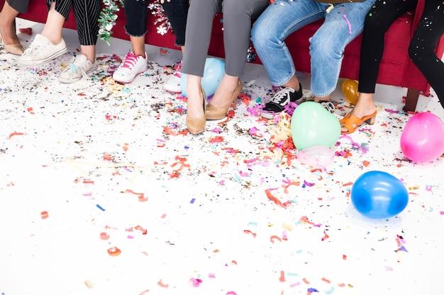 Benen van mensen die op bank zitten die met confettien tijdens nieuwe jaarpartij wordt behandeld.