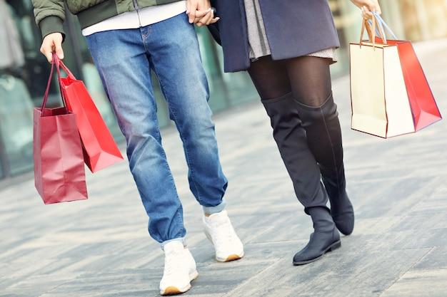 Benen van paar met boodschappentassen na het winkelen in de stad glimlachen en knuffelen