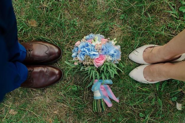 Benen van pasgetrouwden op groen gras. stijlvolle schoenen van bruid en bruidegom buitenshuis. bruids boeket op groen gras close-up. stijlvolle dames- en herenschoenen. trouwdag. bruiloft details. bruiloft.