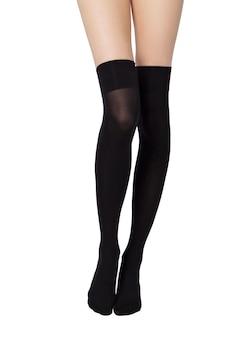 Benen van sexy jonge blanke vrouw in zwarte nylon panty op witte achtergrond