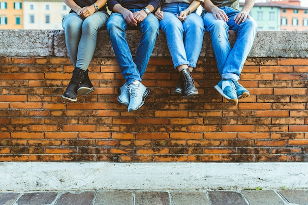 Benen van vier tieners die op een bakstenen muur zitten