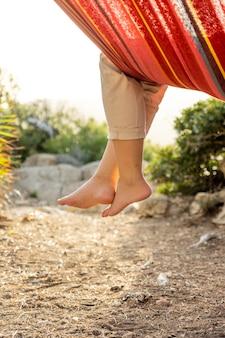 Benen van vrouw hangend aan hangmat in zonsondergang