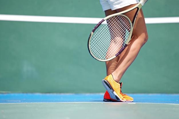 Benen van vrouwelijke tennisspeelster op de baan