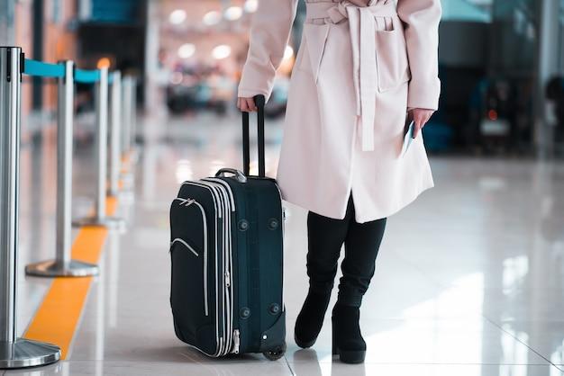 Benen van zakenvrouw met bagage in luchthaven.
