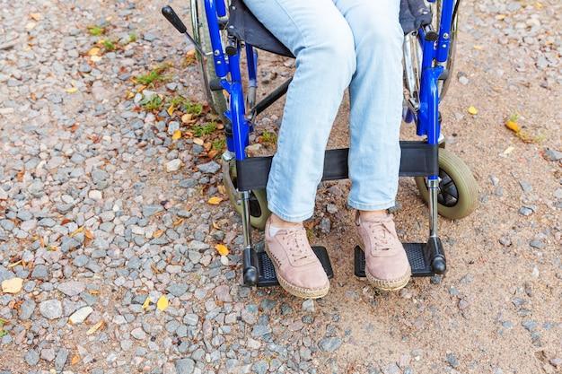 Benen voeten handicap vrouw in rolstoel wiel op weg in ziekenhuis park wachten op patiëntendiensten. onherkenbaar verlamd meisje in invalide stoel voor gehandicapten buitenshuis. revalidatie concept.
