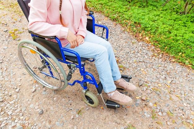 Benen voeten handicap vrouw in rolstoel wiel op weg in ziekenhuis park
