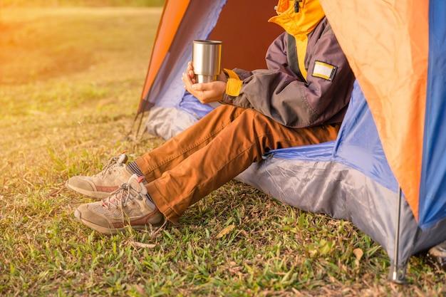 Benen zichtbaar vanaf de tent op de camping in wilde houten achtergrond
