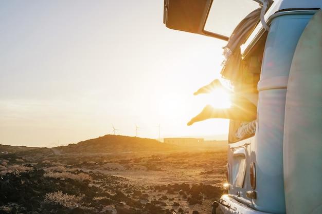 Benenmening van gelukkig surfermeisje binnen minivan bij zonsondergang