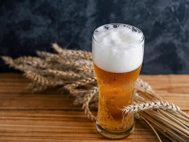 Beneveld glas licht bier op een houten tafel en tarwe