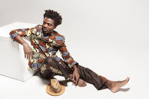 Benieuwd afro man in traditionele nationale kleding zit op kubus. binnen, geïsoleerd op grijze achtergrond