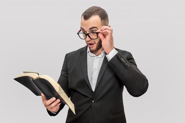 Benieuwd en opgewonden jongeman houdt boek in de ene hand en bril met een andere. hij kijkt in boek. man draagt pak.