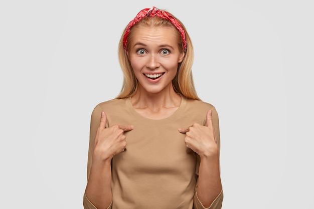 Benieuwd gelukkig vrouwtje met verbaasde vrolijke uitdrukking wijst naar zichzelf, vraagt of ze echt winnaar is, kan niet in succes geloven, draagt rode hoofdband en casual beige trui, geïsoleerd