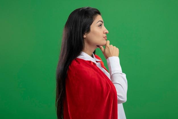 Benieuwd jong kaukasisch superheldmeisje dat zich in profielmening bevindt die hand op kaak zet die recht kijkt geïsoleerd op groene achtergrond met exemplaarruimte