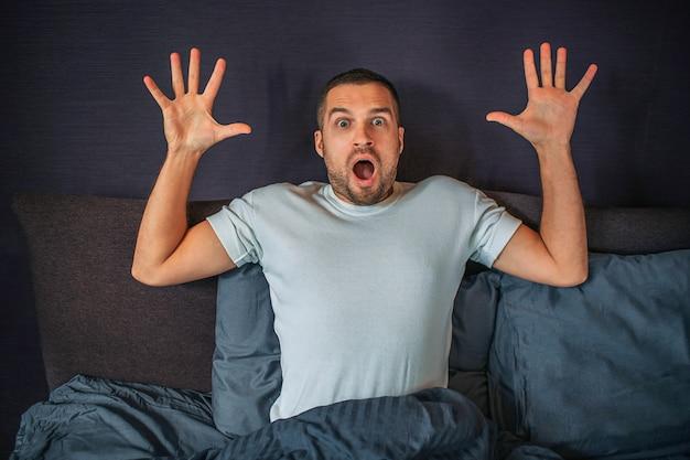 Benieuwd jonge man zit op bed en kijkt rechtdoor camera. hij houdt zijn handen omhoog. guy is bang en bang.