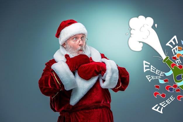 Benieuwd naar de kerstman in een bril met een grijze baard en opgeheven armen op een blauwe achtergrond