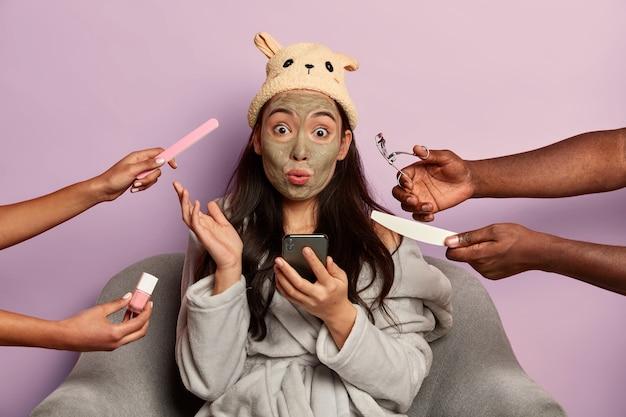 Benieuwd vrouw met geschokte uitdrukking, mobiele telefoon gebruikt tijdens schoonheidsbehandeling