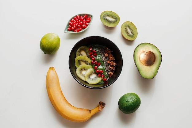 Benodigdheden voor het koken van een smoothiekom. blake bord gegarneerd met kiwi, banaan, granaatappelpitjes, limoen, granola, chiazaad. gezond ontbijt. ronde compositie.