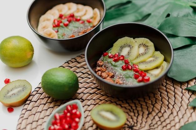 Benodigdheden voor het koken van een smoothiekom. blake bord gegarneerd met kiwi, banaan, granaatappelpitjes, limoen, granola, chiazaad. gezond ontbijt. tropische sfeer.
