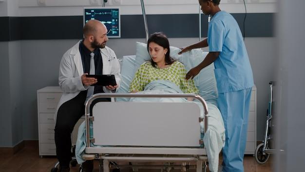 Beoefenaar arts arts legt ziekte-expertise uit aan zieke vrouw